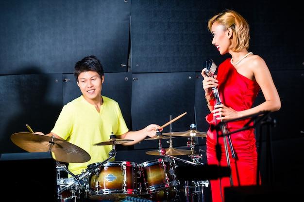 Азиатская профессиональная группа записывает песню в студии