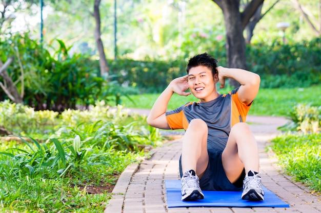 フィットネストレーニングのため腹筋をしているアジア人