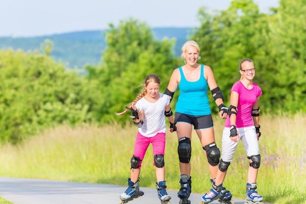 国の車線でスケートを持つ家族のローラーブレード