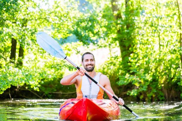 ウォータースポーツのための川でカヤックを漕ぐ男
