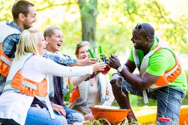 ビールを飲みながら森の中のスポーツの後の友人のバーベキュー