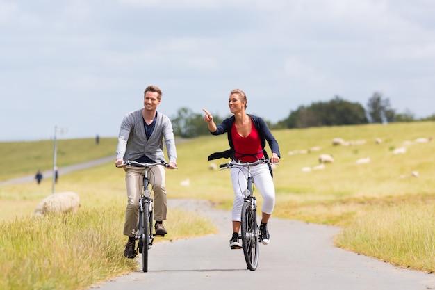 堤防で海海岸自転車ツアーを持っているカップル