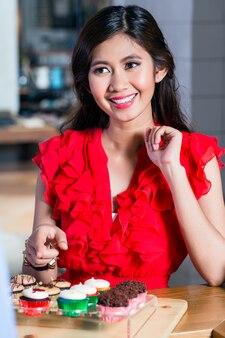 おいしいカップケーキを買う美しいアジアの女性の肖像画