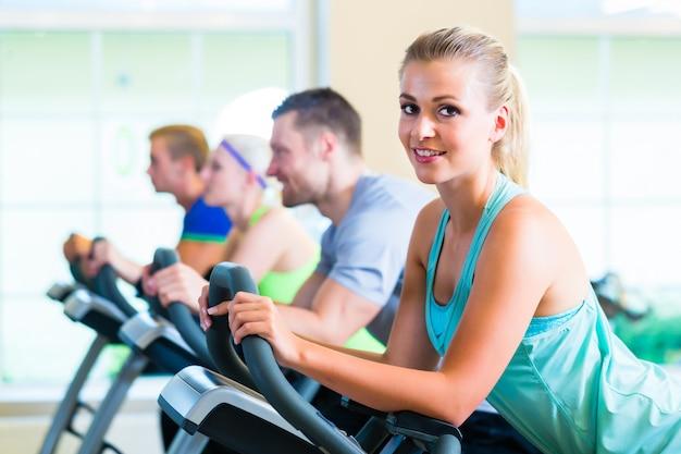 Группа в тренажерном зале, спиннинг на спортивный велосипед