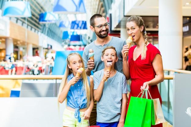 家族のバッグとショッピングモールでアイスクリームを食べる