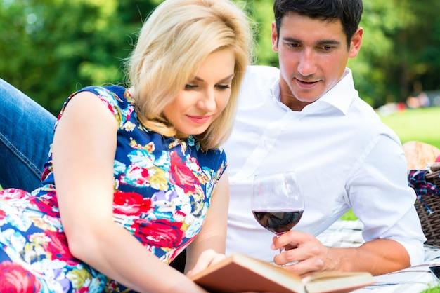 ピクニックを持っている牧草地で本を読んでワインを飲むカップル