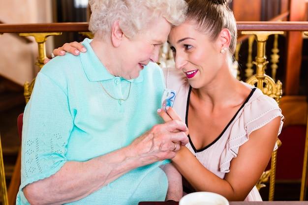 Старшая женщина и внучка на кофе в кафе