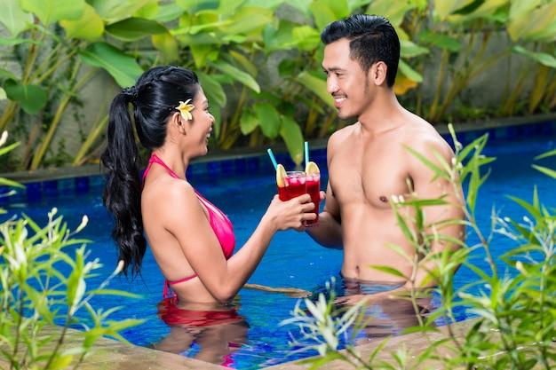アジアのプールで飲み物を持っているカップル