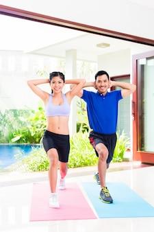 熱帯の家でのスポーツトレーニングでアジアフィットネスカップル