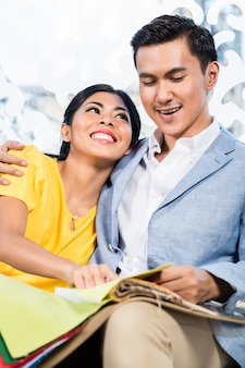 アジアのカップルが家具店でソファを買う