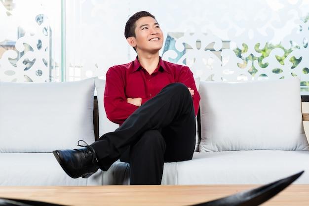 アジアの男が家具店でソファーに座っていた