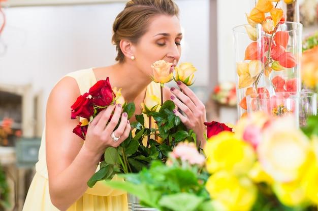 Флорист женщина, пахнущие на розы
