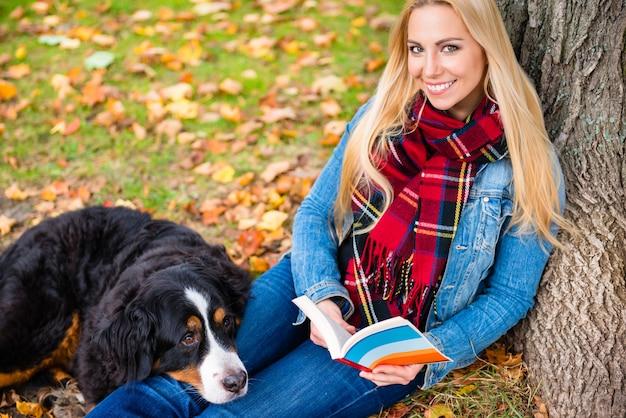 秋の公園で本を読んでいる犬を持つ女性