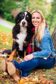 Женщина обнимается с собакой на улице в парке