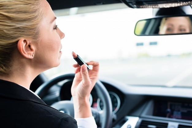彼女の車を運転している間女性が口紅を使用して