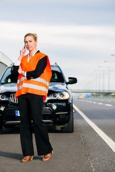 牽引会社を呼び出す車の故障を持つ女性