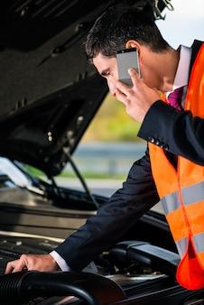 修理サービスを呼び出す車のエンジンの問題を持つ男