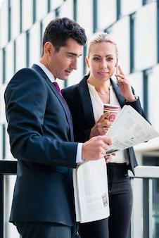 ビジネスの男性と女性と紙と電話