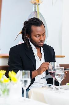 レストランでタブレットを持つビジネス男