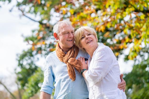 Старший мужчина и женщина, обнимая друг друга в любви