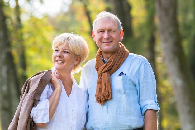 Пожилые супружеские пары, имеющие прогулку в лесу