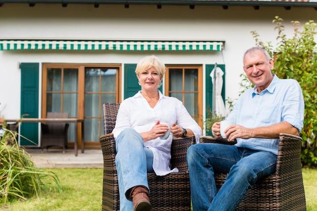 年配の男性人と女性が家の前に座っています。
