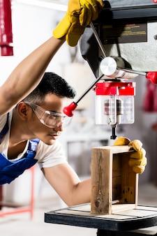 生産工場でのドリルのアジア人労働者