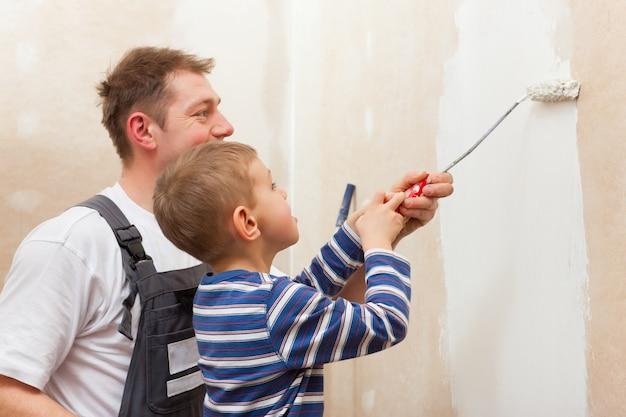 Отец красит стену с ребенком