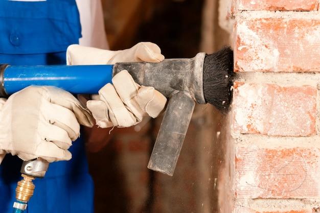 壁を掃除する建設労働者
