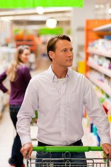 男と女のショッピングカートとスーパーマーケット
