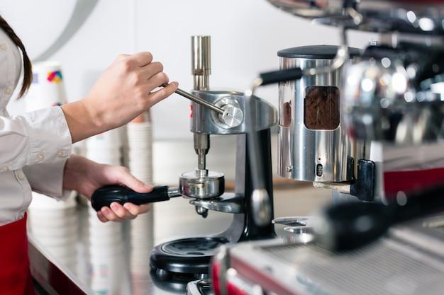 Официант готовит эспрессо на автоматической кофемашине