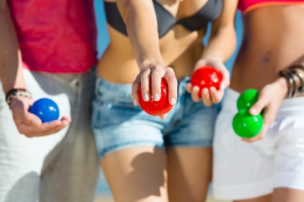 Мужчины и женщины играют в були на пляже