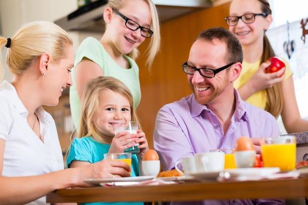 Семья дома завтракает на кухне