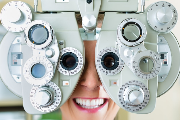 Молодая женщина в фороптер для проверки зрения