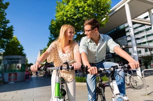 都会のカップルが街で自由時間に自転車に乗る