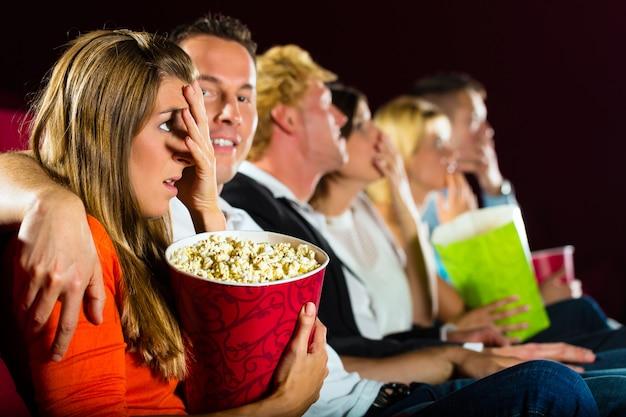Молодые люди смотрят фильм в кинотеатре