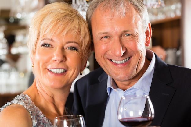 手でワインのグラスとバーで年配のカップル
