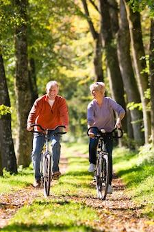 Пожилые люди тренируются на велосипеде