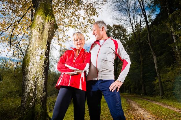 Сеньоры занимаются спортом на лесной дороге