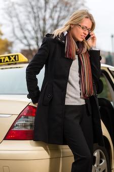 Молодая женщина перед такси с телефоном