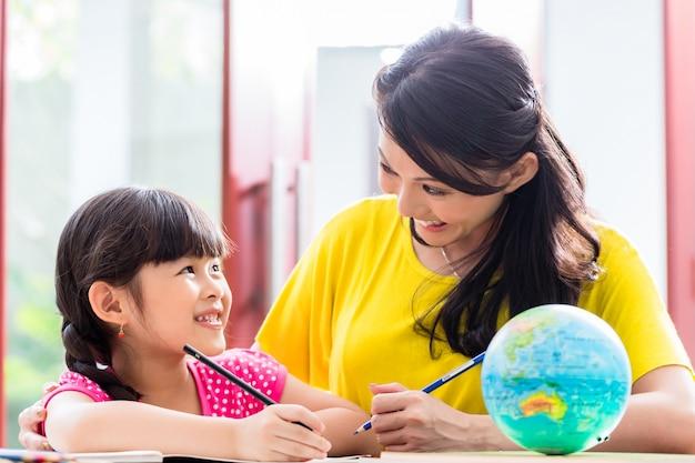 子供と学校の宿題をしている中国人の母親