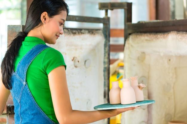 手作りの陶器を持つアジアの女性