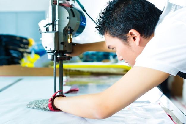 Работник с помощью машины на китайском заводе