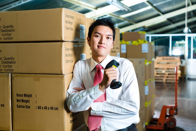 Молодой человек на складе со сканером