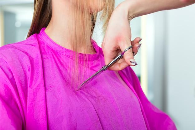 美容院やスタイリストからのヘアカットを受ける女性