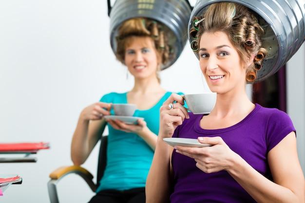 Женщины у парикмахера сушат волосы