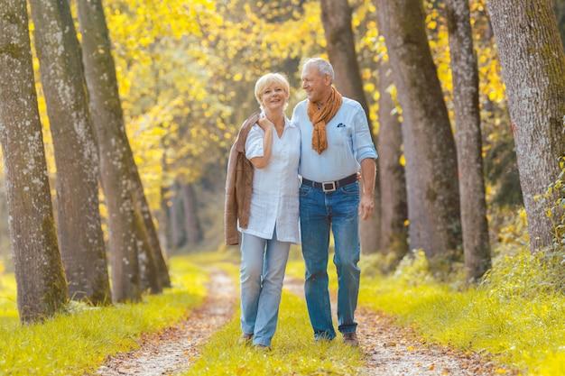レジャーを持っている年配のカップルが森の中を歩く