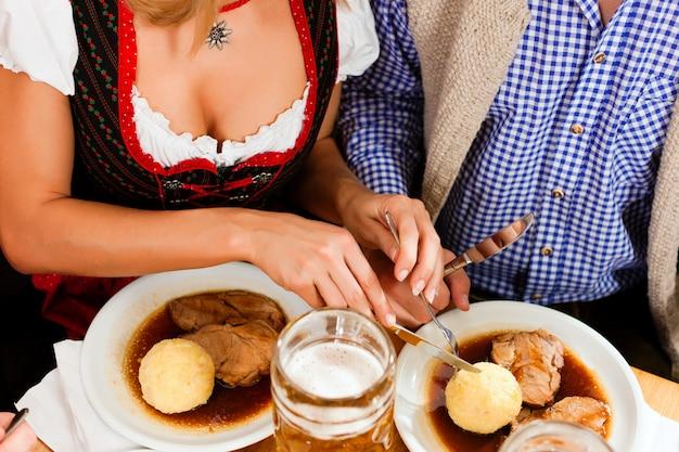 バイエルンのレストランでローストポークを食べるカップル