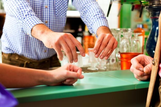 Бармен наливает крепкие напитки в бокалы