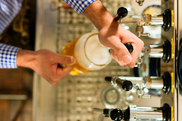 Мужчина рисует пиво из крана